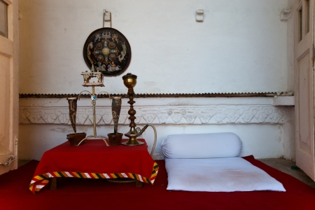 view of an elegant red couch: hookah room with white walls and red floor in old style