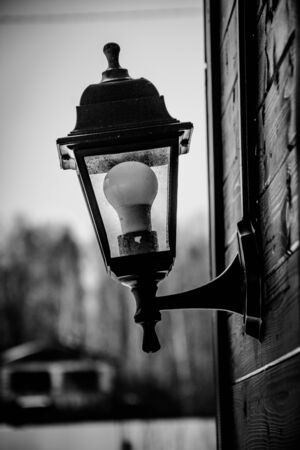 Retro street lamp on a wooden house