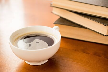 a Cup of black coffee on a wooden table with hardcover books in the background