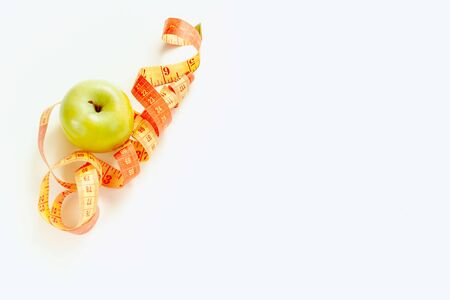 A green Apple and a sewing ribbon are on a white background.The view from the top. the concept of weight loss