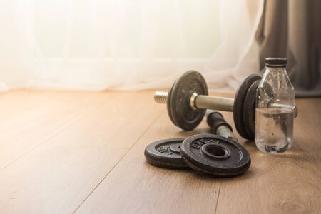 dumbbells for sports at home on the wooden floor for the period of isolation. disk for bodybuilding.