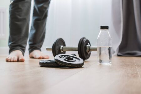dumbbells for sports at home on the wooden floor for the period of isolation. disk for bodybuilding. man on a blurry background