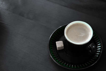 coffee Cup with a piece of cane sugar on a dark wooden background Stockfoto