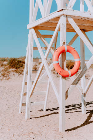white rescue post with a lifebuoy. on a Sunny summer day. Coastal architecture. Wooden rescue post against the blue sky