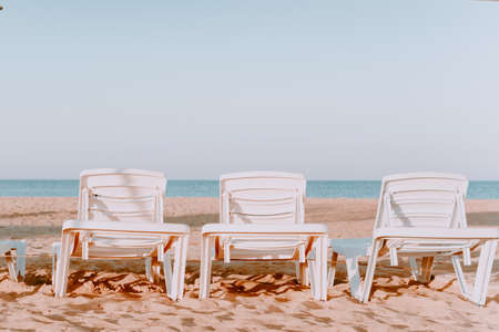 A row of three sun loungers with sea views. Sunny beach with three sun loungers. On a Sunny summer vacation. horizontal image.Beach chairs by the sea in neutral colors.