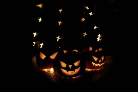 Halloween background. happy Spooky pumpkin head or jack lantern smiley funny horror magic face soft focus on dark background with bokeh of cross shape. October Halloween design concept