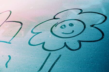 Smiley face flower freehand drawing above a blue ocean color dirty tail car window glass texture with finger dust for background with copy space waiting for water clean or car wash business concept