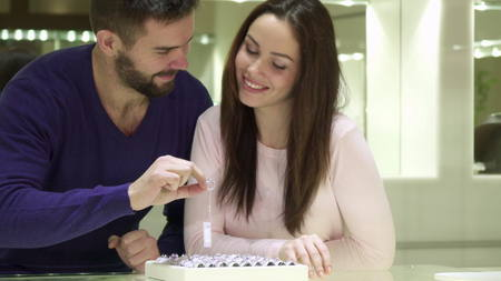 Young couple chooses engagement rings at the jewelry shop