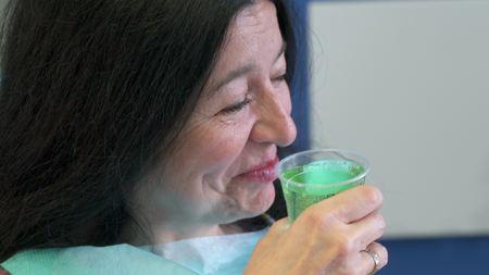 Femme se rince la bouche avec un traitement
