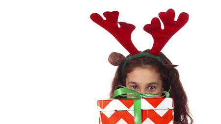 A sweet girl hides behind a Christmas gift box