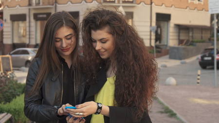 Female friends watch photos on smartphone