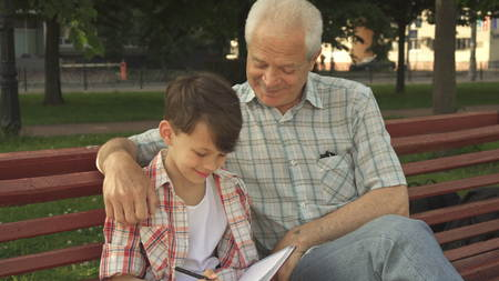 Little boy writes in his notebook what his grandpa says Stock Photo