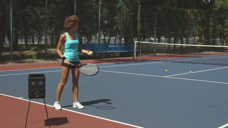 Curly woman hitting tennis balls