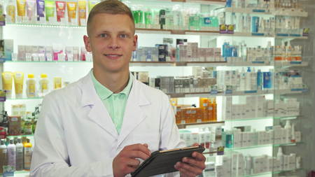 Druggist using tablet and smiling at camera close up
