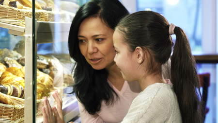 Mother and daughter shopping at the bakery choosing pastry in the showcase 版權商用圖片