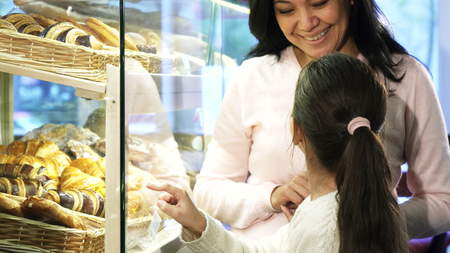 Adorable little girl choosing pastry in the showcase while shopping with her mother Banco de Imagens