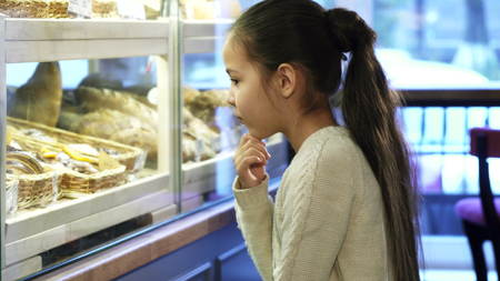 Cute little girl looking at the display at the local bakery