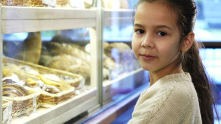 Close up shot of a pretty little girl posinting at the desserts at the bakery