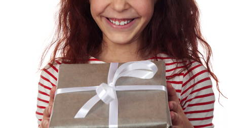 Close-up of a happy girl face with a New Year gift in hands