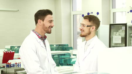 Two colleagues of laboratory assistants communicate during a break at work Stock Photo