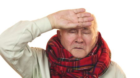 Sick grandpa wearing a scarf touching forehead having fever