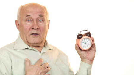 Senior man looking shocked checking time on alarm clock