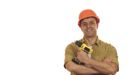 Cheerful mature builser in hardhat posing with a drill machine