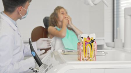 Unhealthy tooth model on the foreground dentist working with child Stockfoto