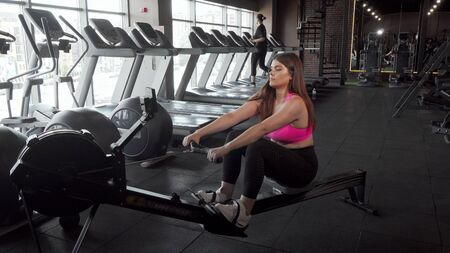 Beautiful curvy sportswoman working out on rowing machine at the gym