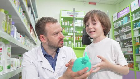 Mature male pharmacist talking to a little boy at drugstore Banco de Imagens