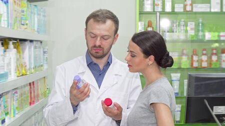 Mature male chemist helping his female customer choosing between two items