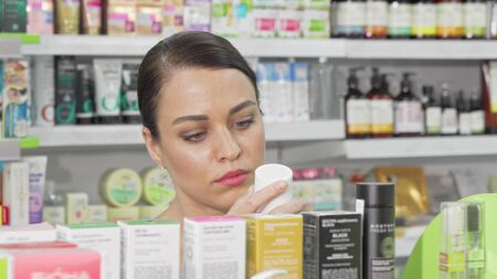 Beautiful woman choosing cosmetic products from the shelf at drugstore