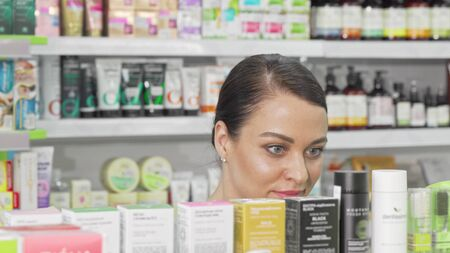Beautiful woman examining products on sale at local drugstore 写真素材