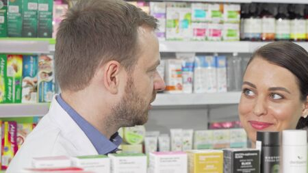 Male pharmacist and his female customer discussing products on sale