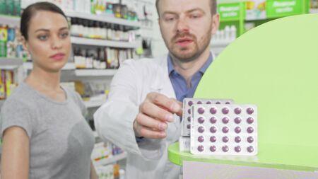 Male pharmacist offering his female customer pills in blister Reklamní fotografie
