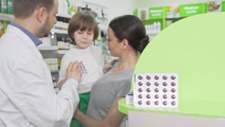 Pharmacist giving blister with pills to a little boy and his mother