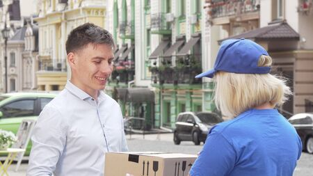 Handsome man examining package delivered by female courier