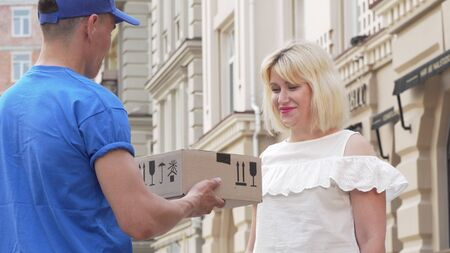 Lovely woman receiving cardboard box parcel from a delivery man Banco de Imagens