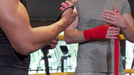Cropped shot of two male boxers wrapping fists in bandages before fighting Stock Photo