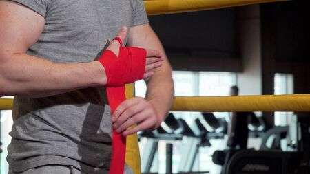 Cropped shot of a male boxer applying wrist bandages before boxing Stock Photo