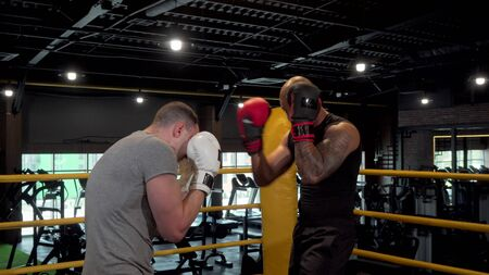 Two male boxers sparring in boxing ring at the gym Stock Photo