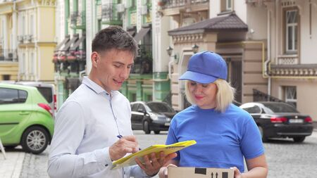 Female courier delivering a package to young man on city street Banco de Imagens