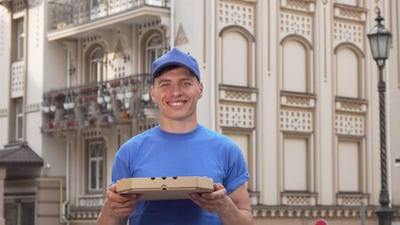 Pizza delivery man holding pizza box standing on the street