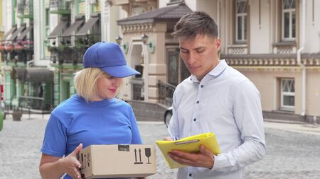 Handsome young man signing papers receiving a package from delivery woman