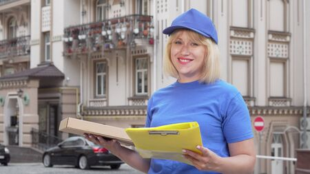 Friendly pizza delivery woman smiling to the camera while working in the city