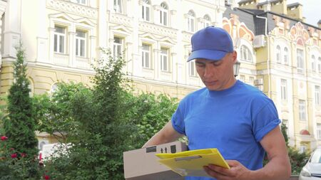 Delivery guy with cardboard box looking for the house of recepient client Banco de Imagens