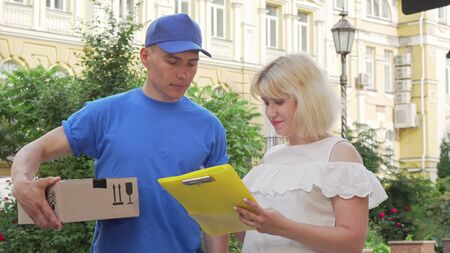 Happy woman signing receipt and receiving a package from courier