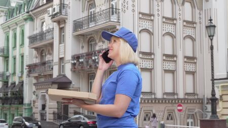 Female courier calling a client delivering pizza in the city