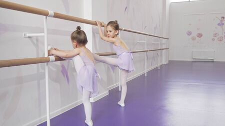 Two cute little ballerinas stretching at ballet school together