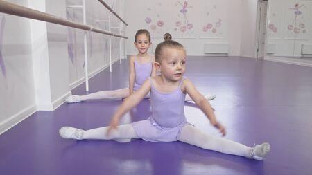 Two cute little ballerinas girls stretching at ballet class doing splits 写真素材
